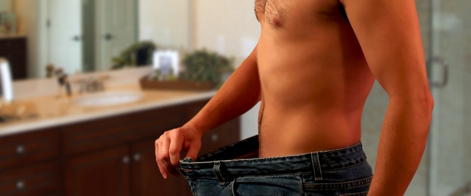 Fit Man Showing Weight Loss in Old Pants